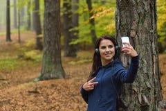 La ragazza ascolta musica e selfie di fabbricazione con lo smartphone in natura Autunno più forrest nei precedenti Immagini Stock