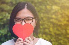 La ragazza asiatica con i vetri dell'occhio, prende un cuore sul fondo delle piante Fotografia Stock