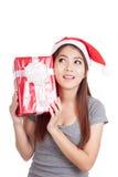La ragazza asiatica con il cappello di Santa pensa che cosa dentro un contenitore di regalo Fotografia Stock