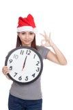 La ragazza asiatica con il cappello rosso di Santa e l'orologio mostrano il segno GIUSTO Immagini Stock Libere da Diritti