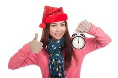 La ragazza asiatica con la manifestazione rossa del cappello di natale sfoglia su e sveglia Fotografie Stock