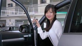 La ragazza asiatica dell'acquirente allegro soddisfatta di nuovo acquisto apre la porta di automobile e mostra le chiavi al centr