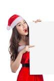 La ragazza asiatica di Natale con Santa Claus copre la tenuta del segno in bianco Fotografia Stock Libera da Diritti