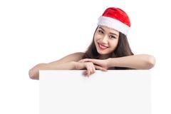 La ragazza asiatica di Natale con Santa Claus copre la tenuta del segno in bianco Fotografie Stock Libere da Diritti