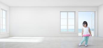 La ragazza asiatica divertente del bambino con gli occhiali da sole nella vista vuota del mare scherza la stanza della casa di sp Immagini Stock Libere da Diritti