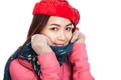 La ragazza asiatica felice con il cappello rosso di natale e la sciarpa ritengono il freddo Immagini Stock