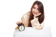 La ragazza asiatica felice sveglia con il cuscino e la sveglia Fotografia Stock