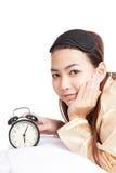 La ragazza asiatica felice sveglia con la maschera di occhio e la sveglia Fotografia Stock Libera da Diritti