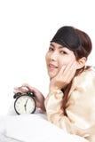 La ragazza asiatica felice sveglia con la maschera di occhio e la sveglia Fotografia Stock