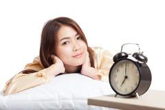 La ragazza asiatica felice sveglia con la sveglia Fotografia Stock