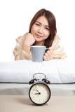 La ragazza asiatica felice sveglia con la tazza di caffè e della sveglia Immagini Stock Libere da Diritti