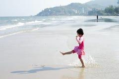La ragazza asiatica gioca sulla spiaggia e gode di di nuotare nel mare dentro immagine stock libera da diritti