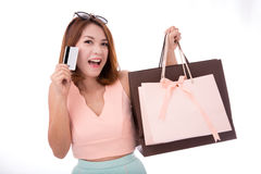 La ragazza asiatica gode di di comperare con la carta di credito ed il sacchetto della spesa isolati su fondo bianco Immagine Stock