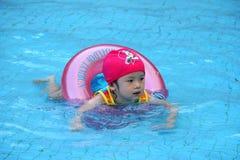 La ragazza asiatica impara nuotare Immagine Stock