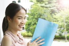 La ragazza asiatica legge un libro blu Fotografia Stock