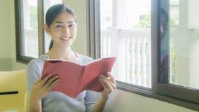 La ragazza asiatica legge un libro rosso Immagini Stock