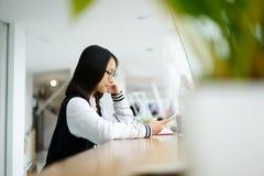 La ragazza asiatica nel coworking avendo ozio sopra irrompe lo shool facendo uso dello smartphone Immagini Stock
