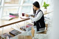 La ragazza asiatica nella chiacchierata coworking con gli amici nelle reti sociali tramite telefono si è collegata al wifi Immagini Stock Libere da Diritti