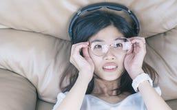 La ragazza asiatica nerd con i vetri sta ascoltando musica immagini stock libere da diritti