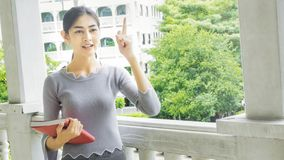 La ragazza asiatica pensa un'idea con il libro rosso Fotografie Stock