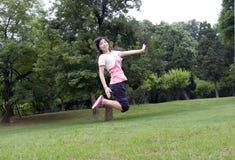 La ragazza asiatica salta Fotografia Stock