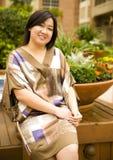 La ragazza asiatica si siede sulla sosta Immagine Stock