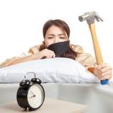 La ragazza asiatica sonnolenta sveglia la sveglia di colpo con il martello Fotografie Stock Libere da Diritti