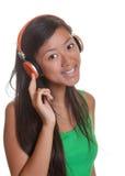 La ragazza asiatica sorridente ascolta la musica Fotografia Stock