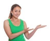 La ragazza asiatica sportiva presenta qualcosa Immagine Stock Libera da Diritti