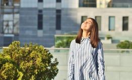 La ragazza asiatica sta camminando giù la via ha vestito la camicia a strisce blu immagini stock