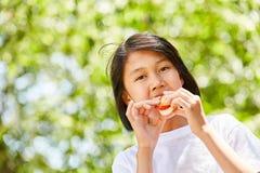 La ragazza asiatica sta mangiando le baguette fotografia stock