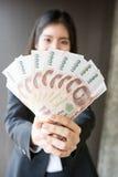 La ragazza asiatica sta mostrando la banconota tailandese Fotografia Stock