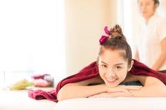 La ragazza asiatica sta sorridendo sul letto tailandese della stazione termale di massaggio Immagine Stock