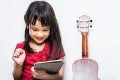 La ragazza asiatica sta utilizzando la sua compressa per imparare giocare la musica Fotografia Stock Libera da Diritti