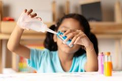 La ragazza asiatica sta versando l'acqua in un vetro fotografia stock libera da diritti