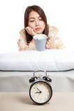 La ragazza asiatica sveglia con la tazza di caffè e della sveglia Immagine Stock Libera da Diritti