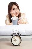 La ragazza asiatica sveglia con la tazza di caffè e della sveglia Fotografia Stock