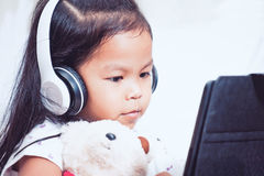 La ragazza asiatica sveglia del piccolo bambino in cuffie sta utilizzando una compressa fotografie stock