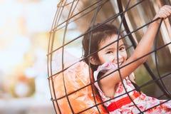 La ragazza asiatica sveglia del piccolo bambino sta giocando le oscillazioni Immagine Stock Libera da Diritti