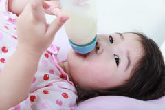 La ragazza asiatica sveglia del primo piano succhia sulla bottiglia per il latte Latte alimentare per il g Fotografia Stock