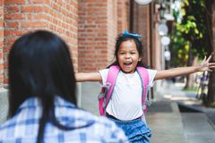 La ragazza asiatica sveglia dell'allievo sta dirigendosi per abbracciare sua madre dopo indietro da scuola fotografia stock