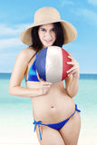 La ragazza asiatica tiene una palla alla spiaggia Immagine Stock