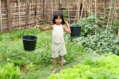 La ragazza asiatica trasporta la benna di acqua Fotografie Stock