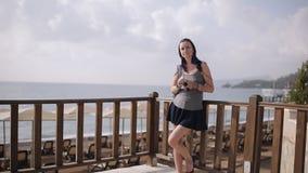 La ragazza aspetta il tipo sulla spiaggia Incontrandosi al litorale video d archivio