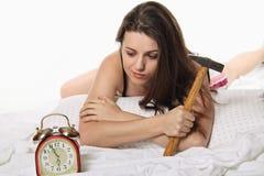 La ragazza aspetta la sveglia con un martello a disposizione Immagini Stock