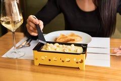 La ragazza assaggia il formaggio fuso e patate del formaggio con un vetro di vino bianco in un caffè Fotografia Stock