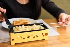 La ragazza assaggia il formaggio fuso e patate del formaggio in un caffè Immagini Stock