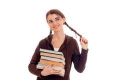 La ragazza astuta allegra dello studente nello sport marrone copre con molti libri in sua una mano che tocca i suoi capelli e sor Fotografia Stock