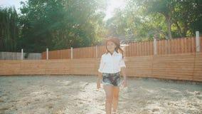 La ragazza astuta cammina e posa ad area del cavallo nel giorno soleggiato 4K archivi video