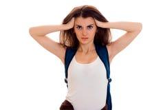 La ragazza astuta dello studente di Anfry nello sport marrone copre con lo zaino sulle sue spalle che esaminano la macchina fotog Fotografie Stock Libere da Diritti